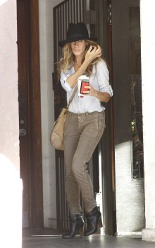 A stylish Sarah Jessica Parker, wearing cuffed corduroy pants and a floppy hat, leaves her apartment building to head to a business meeting with a cup of joe in hand